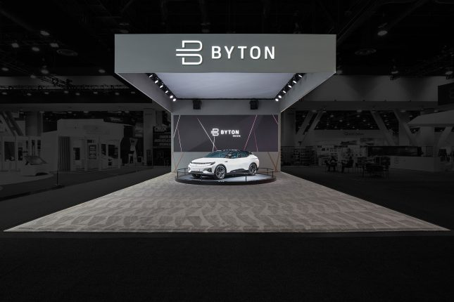 A wide-angle perspective of the Byton Electric Car CES Tradeshow Exhibit with a white automobile on a turntable on grey carpet with a white ceiling and grey walls and a white Byton logo above.