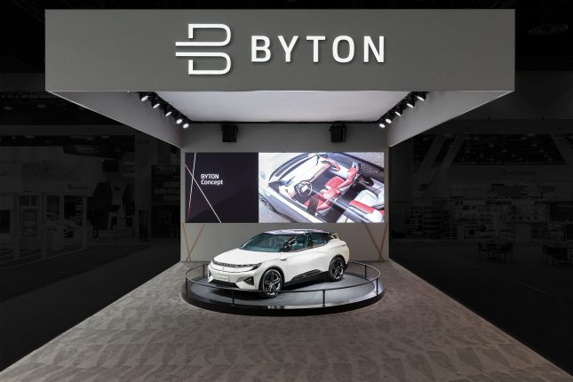 Byton Electric Car CES Tradeshow Exhibit with a white automobile on a turntable on grey carpet with a white ceiling and grey walls and a white Byton logo above.