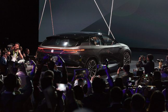 A dark grey Byton concept car rolling down the runway at a press release swarmed by photographers.