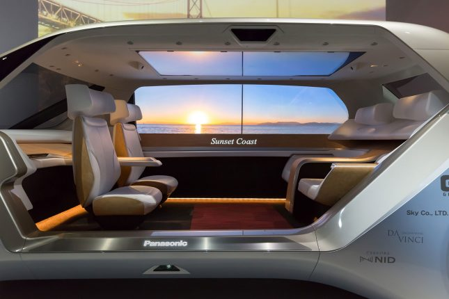 The interior of a panasonic concept vehicle with four light beige seats facing each other and a video screen with a sunset in the background.