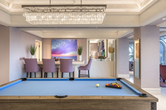 Custom Las Vegas Guest Suite with a Blue Pool table in the foreground, lavender-colored bartools surrounding a bar behind and a wide crystal chandelier above.