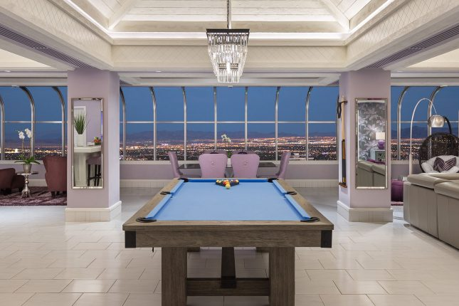 A blue-surfaced pool table in a lavendar-toned hotel room with a dining table and wide city view at dusk in the windows.