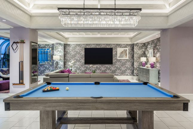 A hotel room with a blue-surfaced pool table in the foreground and a living room with flat-panel TV on silver, patterned wallpaper and a crystal chandelier above.