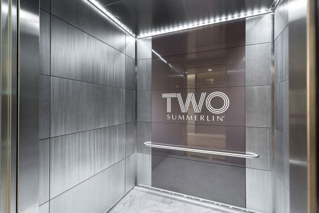 "And elevator interior with shiny silver walls and a grey glass center panel with the words ""Two Summerlin"" written in white and white LED lighting atop."
