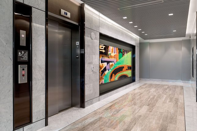An office building elevator lobby with shiny tile floors and walls and a green, orange, black, and purple piece of abstract art hanging alongside a stainless steel elevator door.