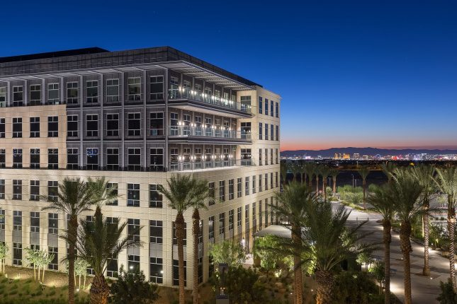 An off-centered perspective of a six-story office building at twilight with beige and grey exterior, three glass balconies, with palm trees and desert lanscaping in the foreground with rich blue skies and the Las Vegas Strip in the background.