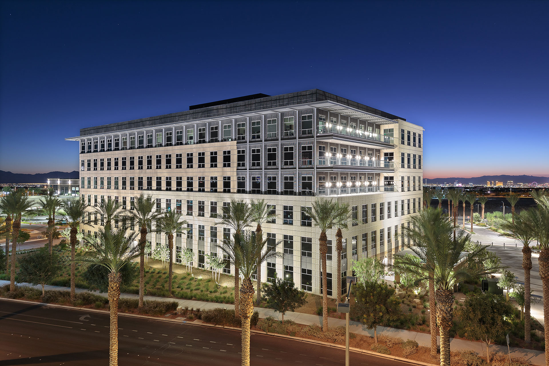 A six-story office building at twilight with beige and grey exterior, three glass balconies, with palm trees and desert lanscaping in the foreground with rich blue skies and the Las Vegas Strip in the background.