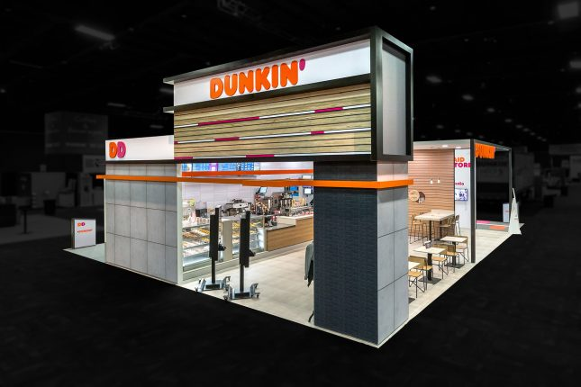 A trade show exhibit which looks like a Dunkin Donuts store clad in grey bricks and tiles and showing the interior counter, display case, and tables from a high perspective and edited so that the area around the exhibit is black and blurred.