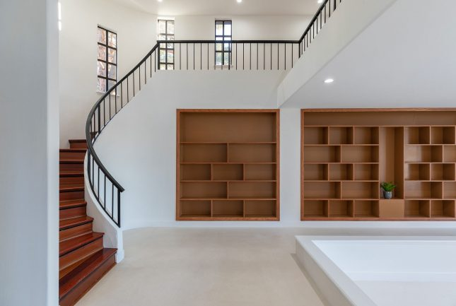 A white room with a brown built-in bookshelf with a spiral staircase wrapping around in with black railings.